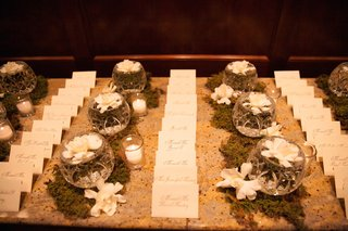 granite-table-with-escort-cards-moss-and-gardenia-flowers