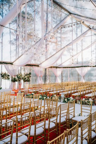 wedding-ceremony-clear-top-wedding-tent-white-drapes-chandelier-lights-gold-chairs-red-carpet