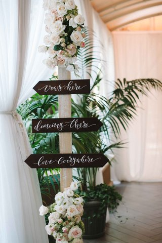 wood-sign-with-white-calligraphy-flowers-on-top-and-base-of-post-for-wedding