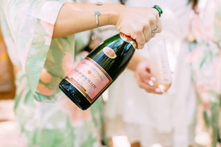 wedding-getting-ready-photos-pink-green-robes-champagne-into-stemless-flutes-while-getting-ready