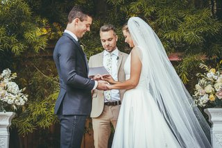 bride-in-stella-york-wedding-dress-groom-in-navy-suit-officiant-in-khaki-suit