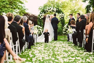 outdoor-wedding-ceremony-greenery-arch-flower-ring-bearer-in-little-suit-at-front-of-ceremony-space
