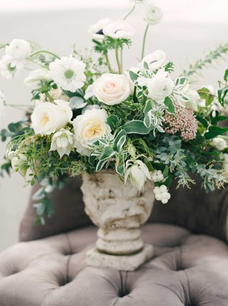 lush-floral-arrangement-with-white-and-blush-flowers-and-lots-of-green-leaves-on-tufted-grey-chair