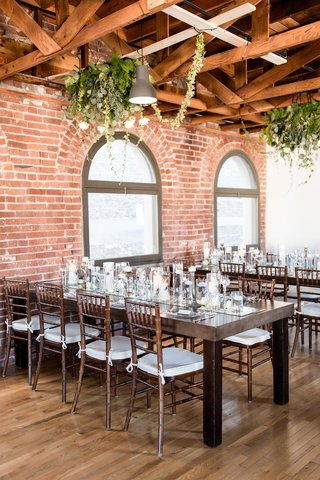 wedding-reception-wood-tables-wood-chairs-mirror-runner-brick-wall-greenery-on-ceiling-can-lights