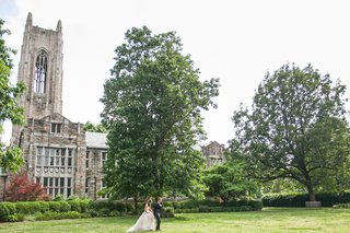 a-bride-and-groom-walk-across-the-grass-lawn-outside-a-church-in-nashville-tennessee