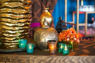 moroccan-style-engagement-party-bar-with-gold-lantern-blue-green-orange-votive-candleholders