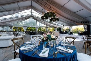 wedding-reception-tent-flower-chandeliers-lounge-area-long-wood-tables-round-table-blue-linen-wood