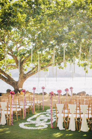 grass-aisle-with-swirled-petals-and-garlands-from-trees