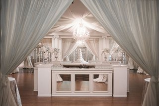mirror-four-sided-bar-with-chandelier-and-drapes-overhead-white-flowers-lights-white-flowers