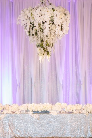 floral-chandelier-above-head-table-lined-with-orchids-and-dresses-with-silver-sequin-linens