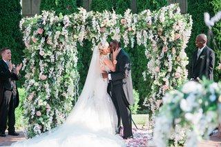 bride-in-galia-lahav-bridal-gown-kissing-groom-under-lush-ceremony-arbor-donathan-hurley-survivor