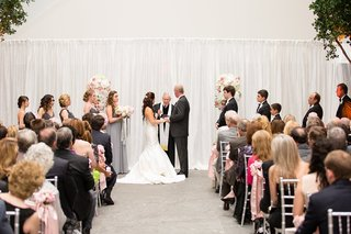 bride-and-groom-saying-vows-against-white-fabric-backdrop-trumpet-dress-white-and-pink-arrangements