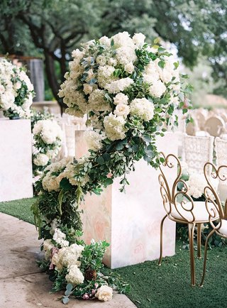wedding ceremony flower print riser podium white hydrangea rose greenery gold garden chair