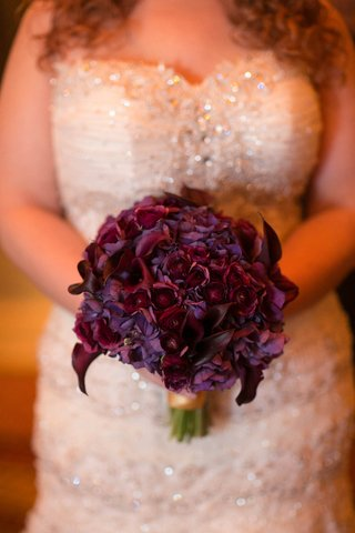 bride-holding-wedding-bouquet-with-purple-flowers-and-calla-lily-blooms