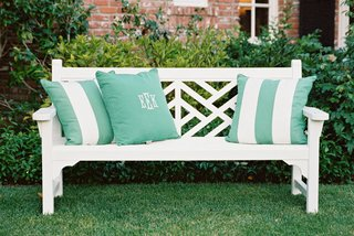 white-bench-on-grass-lawn-at-wedding-with-green-and-white-stripe-and-monogram-pillows