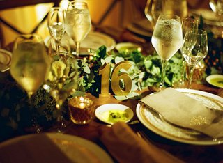 wood-table-with-eucalyptus-leaf-greenery-runner-and-brass-table-number-16-sculpture