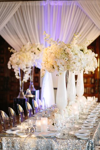 ghost-chairs-silver-sequin-linens-white-vases-orchid-and-rose-centerpieces