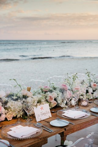 beach-wedding-reception-with-wood-head-table-with-floral-runner-facing-the-water