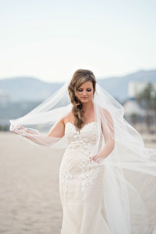 bride-in-ines-di-santo-wedding-dress-playing-with-veil-on-beach-hair-to-side-windy-day-santa-monica