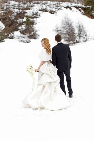 bride-in-white-pick-up-skirt-wedding-dress-with-fur-wrap-shawl-in-snow