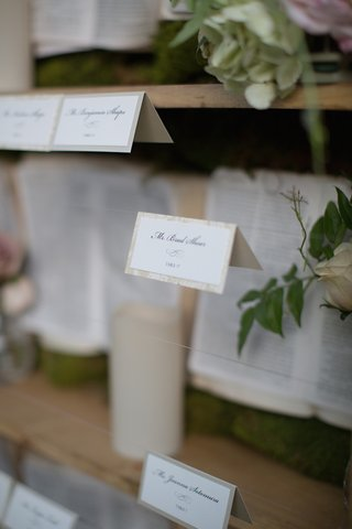 wedding-place-cards-suspended-in-front-of-a-garden-themed-bookcase