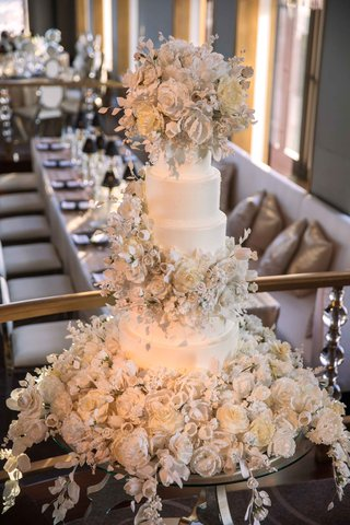 white-wedding-cake-with-hundreds-of-sugar-flowers-and-leaves-cascading-on-cake-and-cake-table