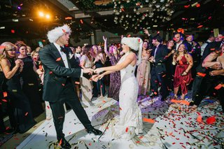 wedding-reception-bride-groom-on-dance-floor-in-holiday-santa-hats-confetti-white-gold-dance-floor