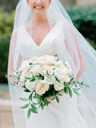bride-in-v-neck-wedding-dress-sareh-nouri-holding-white-rose-bouquet-greenery