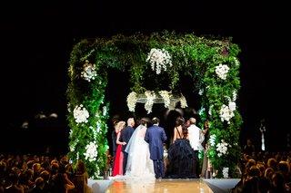 wedding-ceremony-jewish-wedding-under-greenery-chuppah-white-flowers-after-sundown-night-ceremony