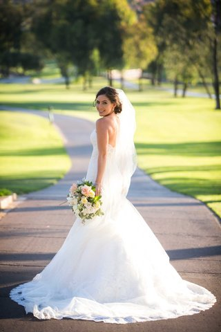 newlywed-woman-smiles-at-camera-in-lace-ines-di-santo-trumpet-gown-holding-white-blush-green-bouquet