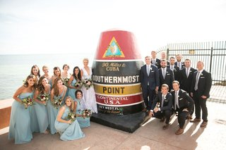bridesmaids-in-blue-dresses-and-groomsmen-with-the-conch-republic-marker-90-miles-to-cuba-sign