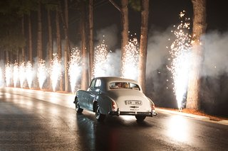 bride-and-groom-in-white-rolls-royce-car-classic-white-with-firework-fountains-lining-path-to-exit