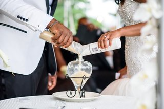 african-american-bride-and-groom-pouring-white-and-tan-sand-into-container-wedding-ceremony