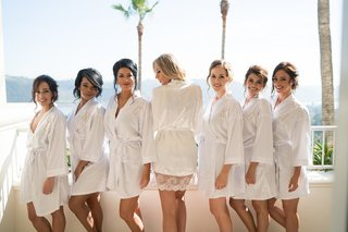 stephanie-ming-with-bridesmaids-in-monogram-white-robes-on-balcony-at-wedding-venue-getting-ready