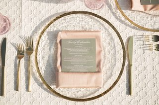 gold-rimmed-transparent-charger-gold-flatware-blush-napkin-grey-menu-textured-white-linens