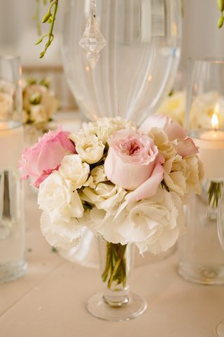 pink-roses-and-white-flowers-surround-base-of-glass-centerpiece-vase