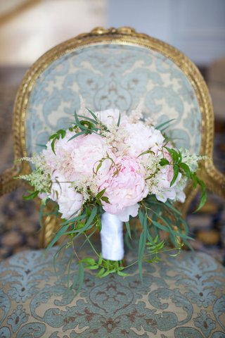 bridal-bouquet-with-greenery-and-fluffy-pink-peonies-wrapped-with-white-satin-ribbon-on-chair