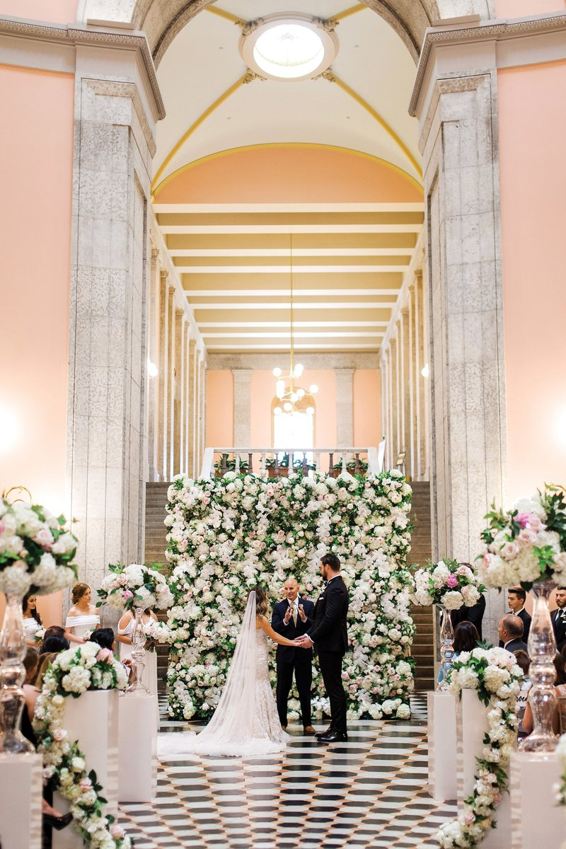 Vow Exchange in Front of Flower Wall