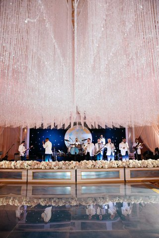 wedding-band-in-white-tuxedo-jackets-performing-under-crystal-ceiling-treatment-at-ballroom-wedding