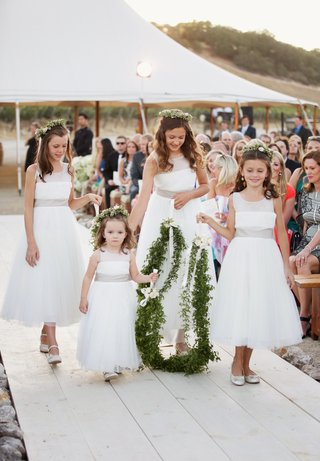 four-flower-girls-walk-down-aisle-holding-garland