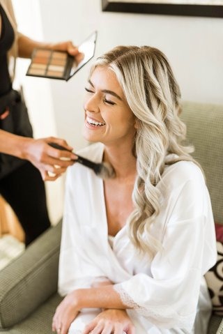 bride-in-white-robe-getting-makeup-done-makeup-artist-brush-long-blonde-hair-laughing