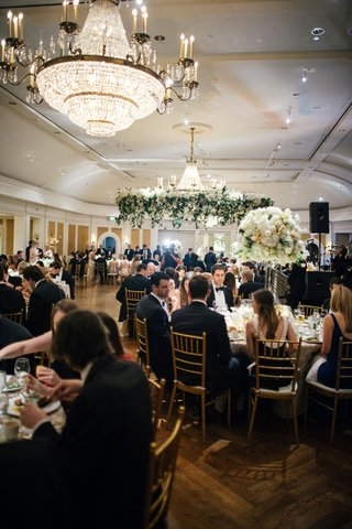 sophisticated-ballroom-wedding-reception-crystal-chandelier-greenery-wreath-over-dance-floor