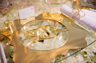glass-table-with-flowers-beneath-glass-gold-charger-plate-die-cut-with-monogram-in-center-laser-cut