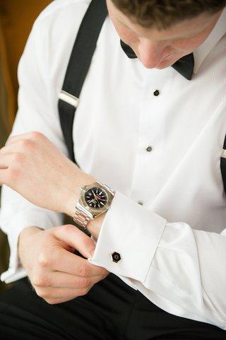 groom-in-suspenders-putting-on-cufflinks-before-wedding