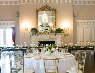 wedding-reception-fireplace-gold-mirror-greenery-white-table-wood-reception-table-head-table-candles