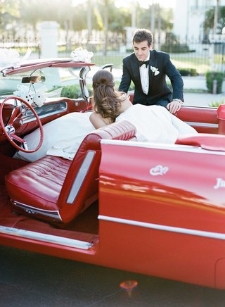 groom-in-tuxedo-helping-bride-out-of-classic-red-car-with-vintage-seats-and-dice-die-hanging-mirror