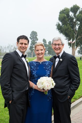 mother-of-groom-in-royal-blue-dress-with-floral-vine-print-bateau-neckline-white-bouquet-tuxedos