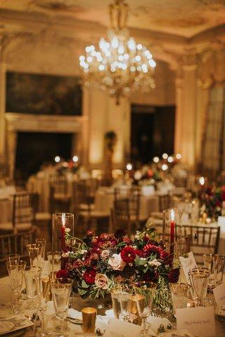 wedding-reception-table-low-centerpiece-burgundy-flowers-dahlias-blush-roses-greenery-fruits-gold