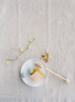 honey-dipper-with-honeycomb-and-robin-eggs-on-small-white-plate