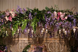 ceremony-arch-with-purple-and-blush-flowers-pink-protea-bloom-greenery-iron-light-fixture